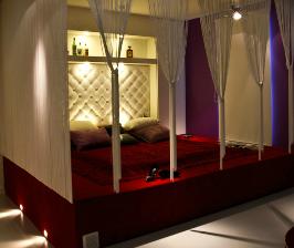 Полутемная спальня с кроватью на красном подиуме: дизайнер Диана Ларина